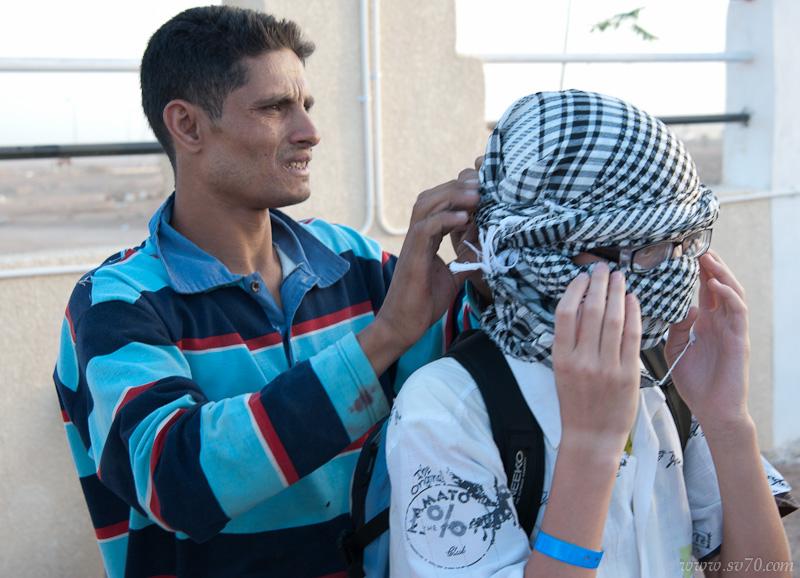 Гид помогает одевать арабский противогаз